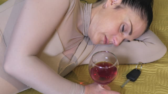 Woman lying near car keys and glass of win - vídeo
