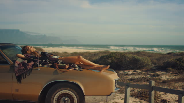 Woman lying on car at the beach video