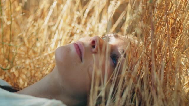 woman lying on meadow - leżeć filmów i materiałów b-roll