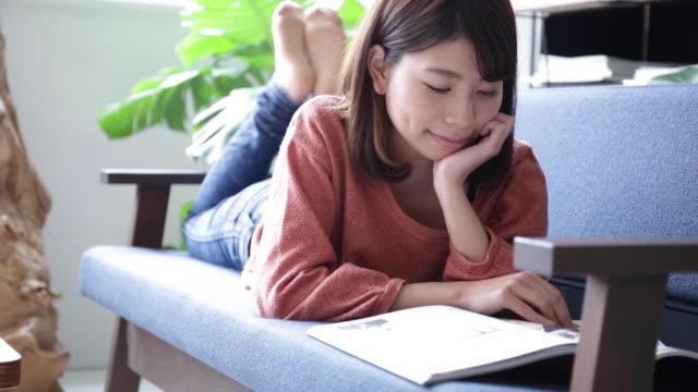 stockvideo's en b-roll-footage met een vrouw liggend op de sofa - woman home magazine