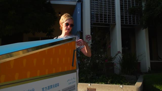 vidéos et rushes de femme postant son bulletin absent à l'urne officielle - une seule femme d'âge mûr