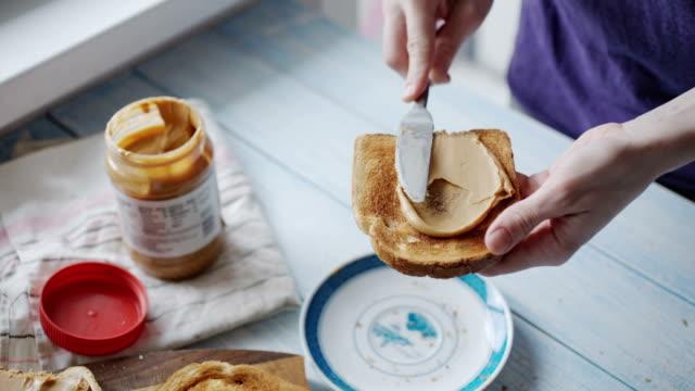 stockvideo's en b-roll-footage met vrouw maakt een boterham met pindakaas - geroosterd brood