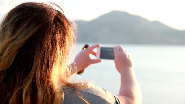 woman makes a sea panorama video on the phone video