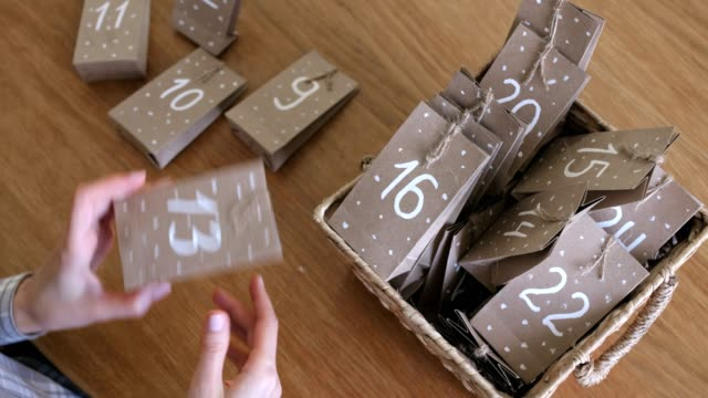 frau macht weihnachts-adventskalender für kinder. schreibt eine nummer auf der tasche mit pinsel und weißer farbe. - advent stock-videos und b-roll-filmmaterial