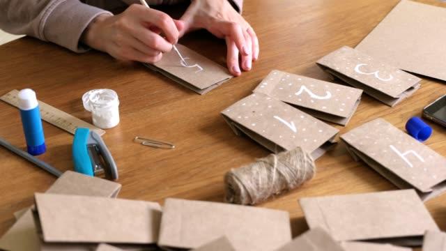 vidéos et rushes de la femme fait le calendrier de l'avent de noël pour les enfants. écrit un numéro sur le sac par la brosse et la peinture blanche. - calendrier de l'avent