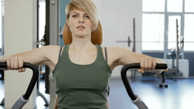 Woman makes exercises for her back The camera moves from the right to the left. Young woman wearing sporty outfit is in the gym. Sporty young smiling woman sits at the training apparatus. Woman actively makes exercises for her back muscles. human back stock videos & royalty-free footage