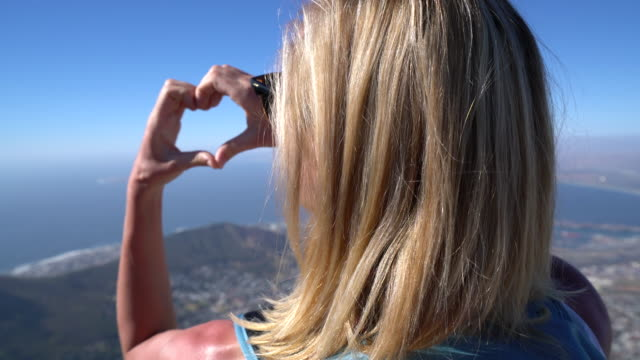 Woman makes heart shape with hand in Cape Town, South Africa Young woman makes heart shape with fingers on top of Cape Town famous Table Mountain. table mountain national park stock videos & royalty-free footage