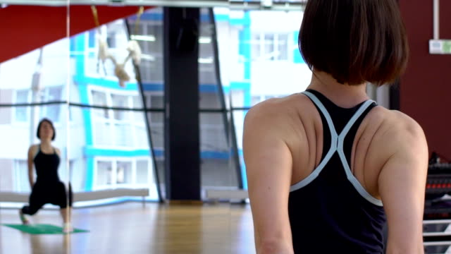 woman makes lunges to stretch her legs and arms in the gym - metodo pilates video stock e b–roll