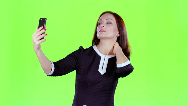 Woman makes selfie on her phone. Green screen video