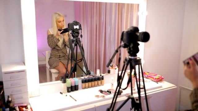 woman make-up artist filming tutorial in make-up studio - influencer стоковые видео и кадры b-roll