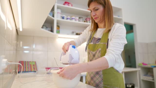 vidéos et rushes de femme faisant un gâteau dans la cuisine domestique - batteur électrique