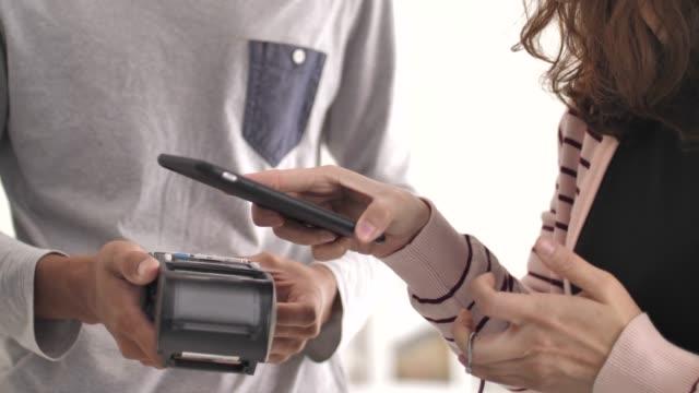 vídeos de stock e filmes b-roll de woman making a contactless payment with phone - pagar