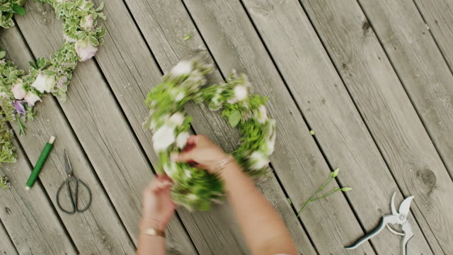 woman making a flower crown on midsummer in sweden - prodotto d'artigianato video stock e b–roll