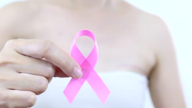 stockvideo's en b-roll-footage met vrouw maken een roze lint - breast cancer