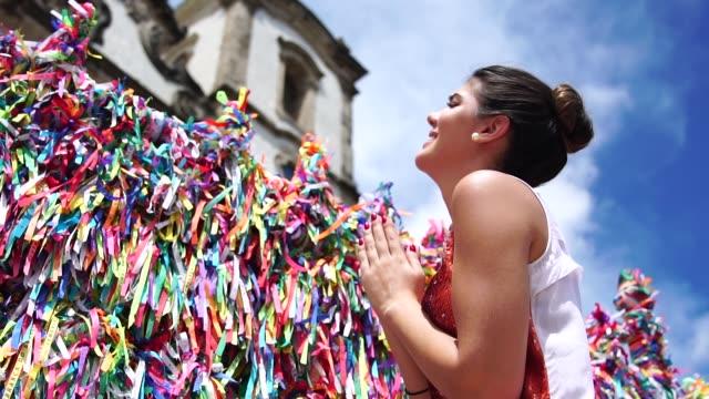 女性サルバドール、バイーア州、ブラジルの教会の塀でブラジルのリボンに願いを作る ビデオ