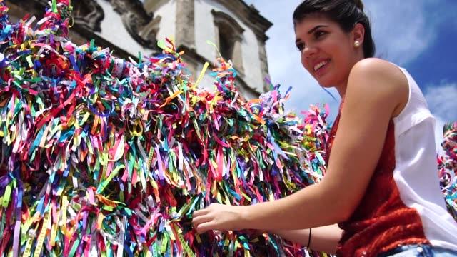 kobieta składająca życzenie z brazylijskimi wstążkami na ogrodzeniu kościoła w salvador, bahia, brazylia - tradycja filmów i materiałów b-roll