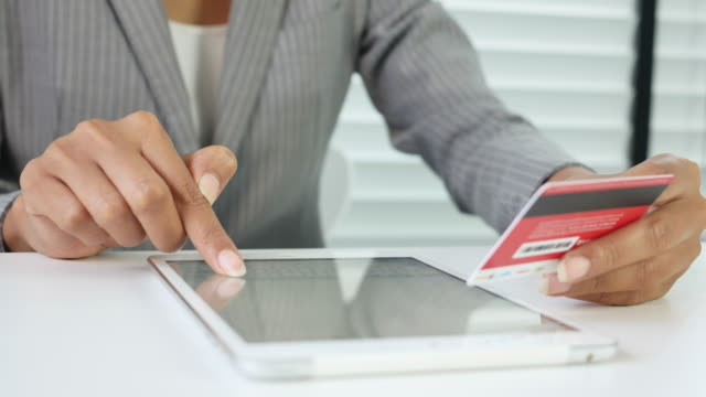 Woman making an online credit card purchase on Digital Tablet Dolly shot Woman making an online credit card purchase on Digital Tablet. Tracking shot gold card stock videos & royalty-free footage