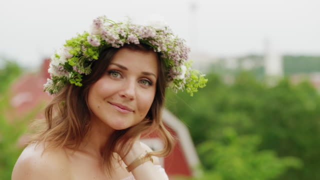 Woman making and wearing a flower crown on midsummer in Sweden - video
