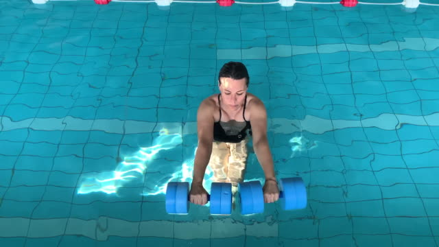 Woman Making Aquatic Gymnastic in the Water in a Swimming Pool