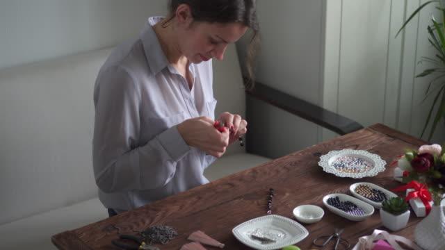 woman making beaded earrings using pliers - браслет стоковые видео и кадры b-roll