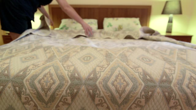 Woman making bed in bedroom Woman making bed in bedroom double bed stock videos & royalty-free footage