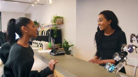 vidéos et rushes de femme faisant le paiement par carte au comptoir dans un magasin de vêtements - faire les courses