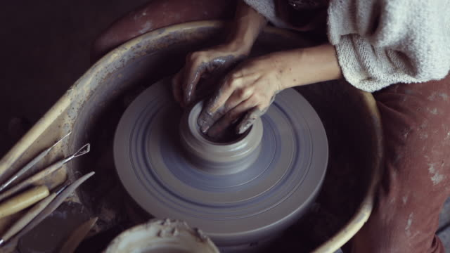 Woman making ceramic work with potter's wheel