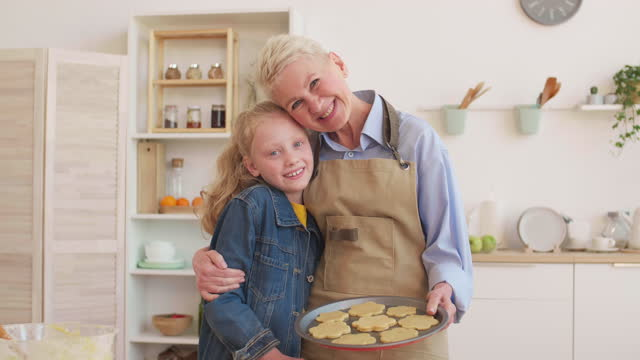 Woman Making Cookies with Granddaughter Medium POV of white-haired elderly Caucasian woman wearing apron holding baking sheet with flower-shaped raw cookies, hugging blue-eyed little granddaughter, then both looking up and smiling on camera granddaughter stock videos & royalty-free footage