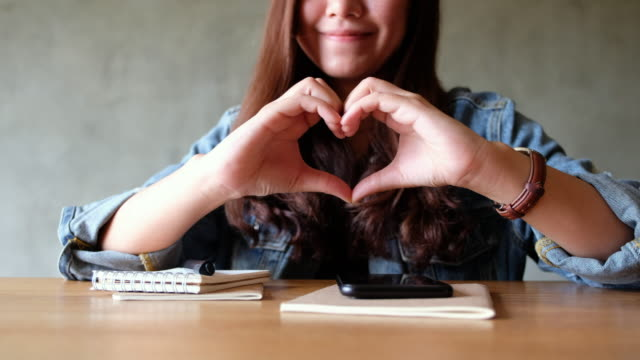 A woman making heart hand sign