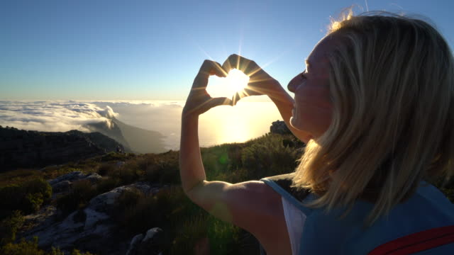 Woman making heart shape with hands on Table Mountain Young woman loving hiking Table Mountain, make heart shape with hands table mountain national park stock videos & royalty-free footage