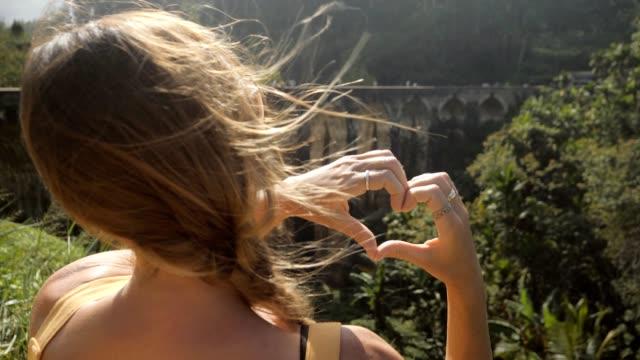 stockvideo's en b-roll-footage met vrouw die hartvorm met handen op theeplantage en oude treinbrug in sri lanka maakt die van het landschap houden en nieuw land in azië reizen dat culturen ontdekt. het hartvorm slow motion van het meisje - camelia white