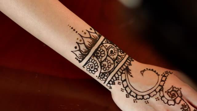 Woman making henna tattoo on hand. 4K video