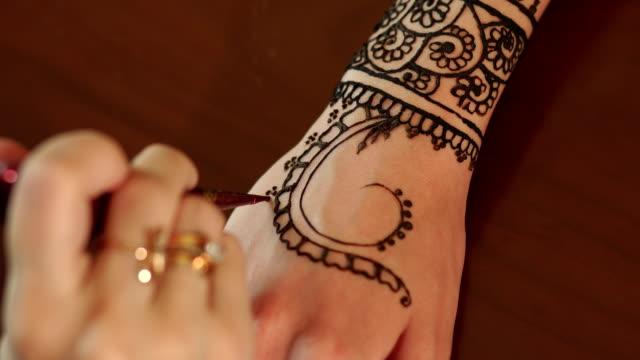 Woman making henna tattoo on hand, close-up. video