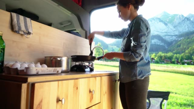 Woman making pancakes  in the van Young Caucasian woman making pancakes  in the van rv interior stock videos & royalty-free footage