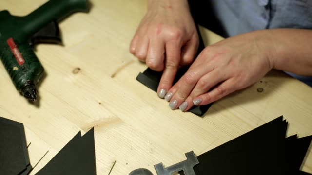 Woman making paper garland with black flags video