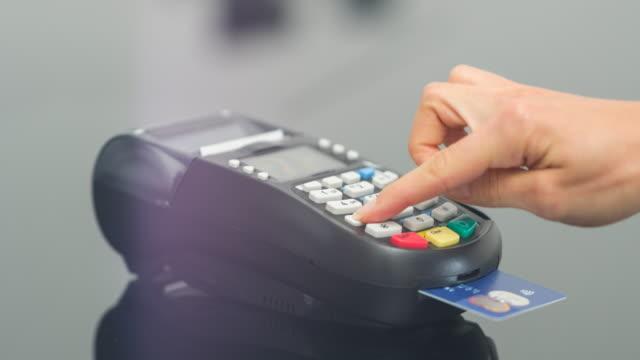 vídeos de stock, filmes e b-roll de mulher fazendo o pagamento com cartão de crédito e inserir o código pin - pin