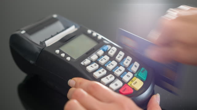 Woman making payment with credit card and entering PIN code Woman sliding credit card in POS terminal and entering PIN code. register stock videos & royalty-free footage