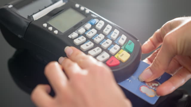 Woman making payment with credit card and entering PIN code Woman inserting credit card in POS terminal and entering PIN code. credit card purchase stock videos & royalty-free footage