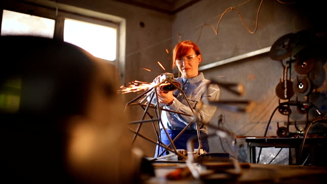 Woman making sculpture using grinding tool Young artist woman sculpturing using grinder, in workshop. Girl power concept girl power stock videos & royalty-free footage