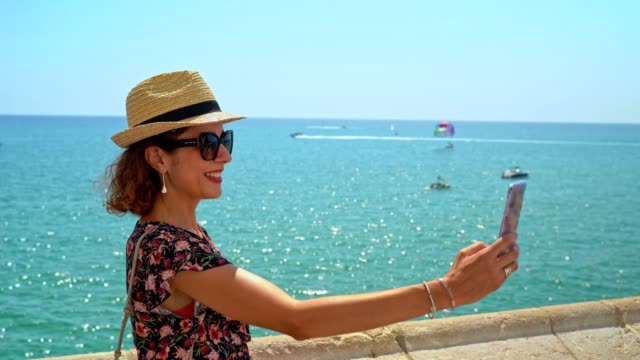 Woman making selfie, face time or taking photo with the mediterranean sea on the background