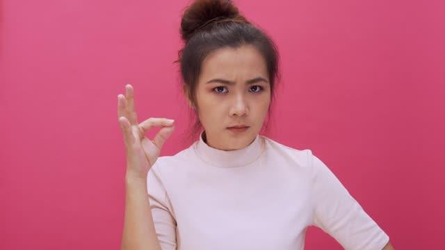 stockvideo's en b-roll-footage met vrouw maken shush gebaar op roze achtergrond 4k geïsoleerd - stilte
