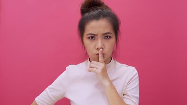 vídeos y material grabado en eventos de stock de mujer haciendo gesto de shush en aislado fondo rosa 4k - dedo sobre labios