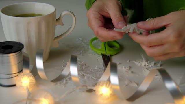 frau macht schneeflocke aus papier - girlande dekoration stock-videos und b-roll-filmmaterial