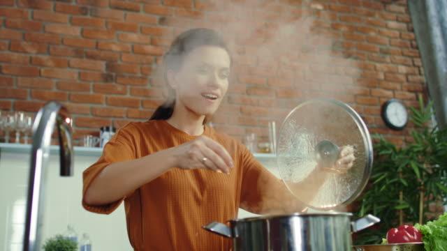 vídeos de stock e filmes b-roll de woman making soup in kitchen. girl adding salt to boiling pot. - cooker happy