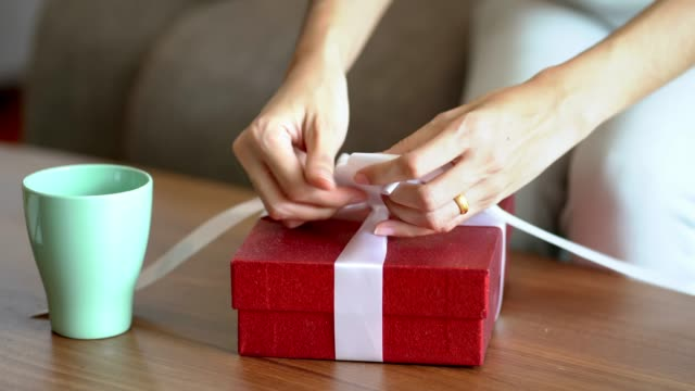 Woman making the package red gift box with white ribbon. Woman making the package red gift box with white ribbon. wrapped stock videos & royalty-free footage