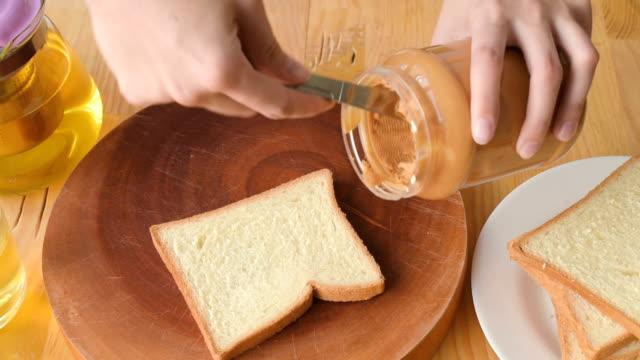 Frau macht leckere Erdnussbuttersandwich. – Video