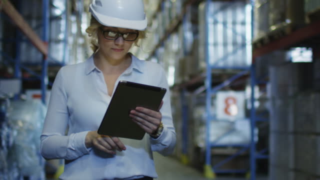 woman manager in hard hat walking in logistic warehouse. holding tablet pc in hands. - deposito per la distribuzione video stock e b–roll