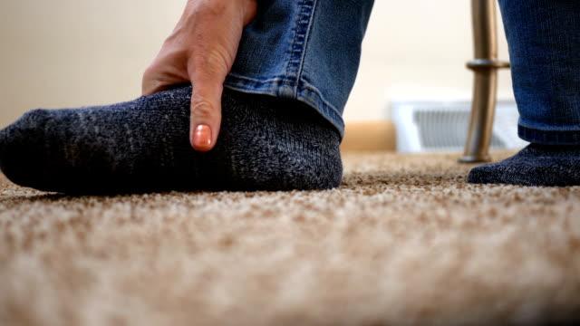 vídeos y material grabado en eventos de stock de mujer masajes su dolorido pie contra el piso de alfombra - columna vertebral humana