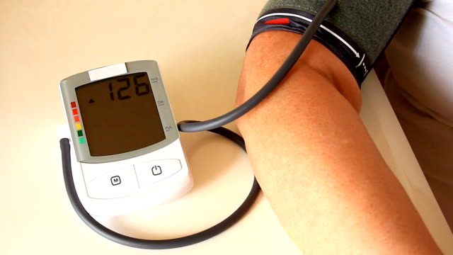 Woman measures blood pressure with instrument of measurement video