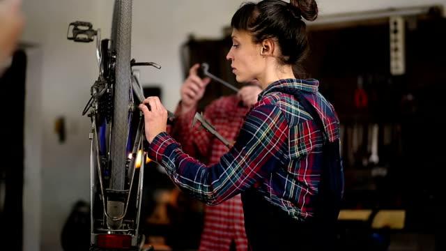 Woman Mechanic is Repairing Bike In Workshop, And Craftsman Assisting video